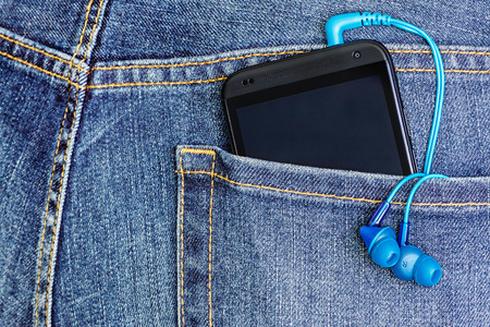 Moscow, Russia - March 18, 2014: HTC Mobile Phone in a jeans pocket. HTC Corporation founded in 1997 by Cher Wang, HT Cho and Peter Chou, the priority was the rapidly developing market of smartphones.