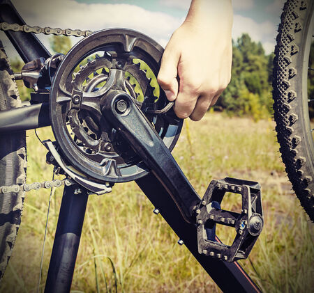 toned image: hand with key repairs bicycle against the sky. toned image Stock Photo