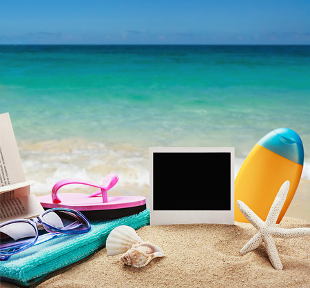 beach accessories and photos on the memory on a background of sea and sand photo