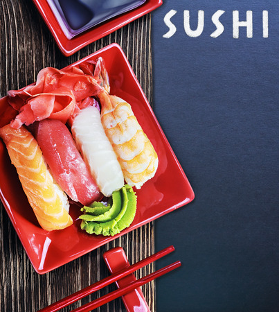 rolls and sushi and chopstick on a black background for text photo