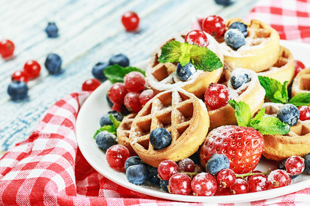 Waffles with fresh berries on the tabla. Focus on berries in the foreground. Shallow depth of field photo