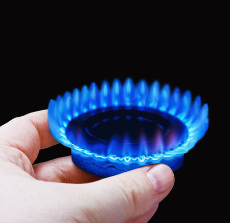 hobs:  Hands holding a flame gas fone. Fokus black on the front edge of the gas hobs
