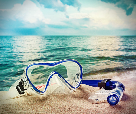 toned image: snorkel and scuba mask on the beach. Toned image