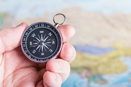 compass in hand over travel map photo