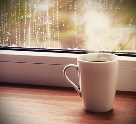 sill: cup of hot coffee on the window sill wet from the rain. Toned image