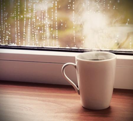 x�cara de ch�: x�cara de caf� quente sobre o peitoril da janela molhada da chuva. Imagem tonificada