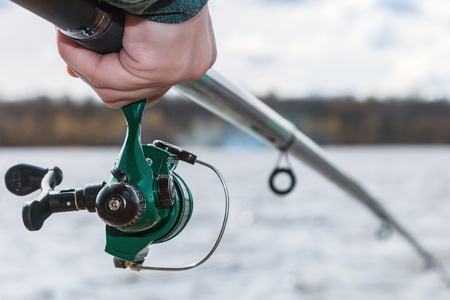 sportfishing: hand holding a fishing rod with reel. Focus on Fishing Reels