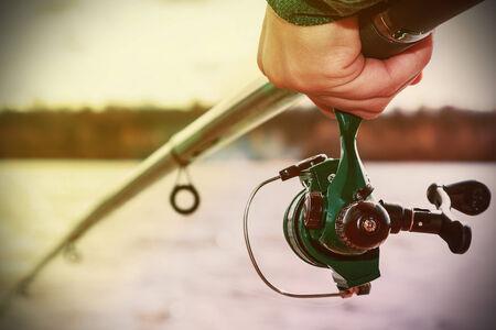 hand die een hengel met reel. Focus op vissen rollen. Getinte afbeelding Stockfoto