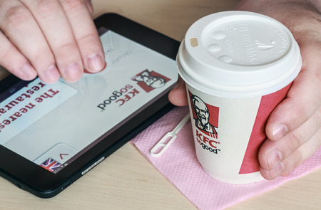 harland: Moscow, Russia - May 22, 2014: Paper cups with coffee KFC logo on the tablet before choosing a man. KFC U.S. chain of cafes catering, specializing in chicken dishes. Was founded in 1952, Harland Sanders