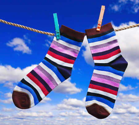 colorful socks hanging on clothespins against the sky with clouds photo
