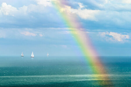 beautiful landscape with a rainbow after the rain and sailboats.focus on the waves in front of the frame and rainbow photo
