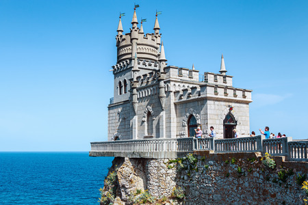 Yalta, Crimea - June 5, 2014: Tourists walking near the Castle Swallows Nest. Swallows Nest architectural and historical monument, located on a steep 40-meter cliff Avrorinoj Cape Ai-Todor.