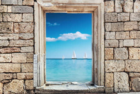 wall of stones with a hole under the door on a background of a sea landscape. Focus on the wall photo