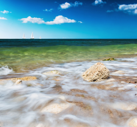 stone washed by the waves and the boat sails on the horizon. Focus on the stone. Photographed using ND filter photo