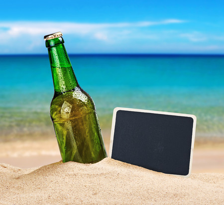 unlabelled: Beer bottle in the sand on the beach and a blackboard for writing