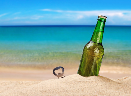 unlabelled: Beer bottle on a sandy beach with clear sky