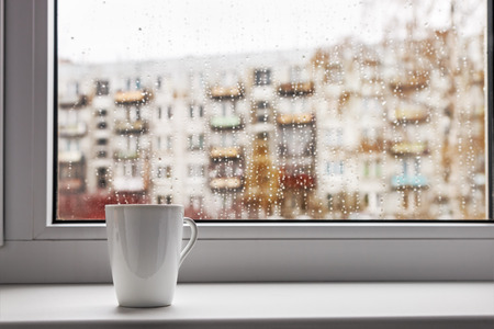 cup of hot coffee on the window sill wet from the rain
