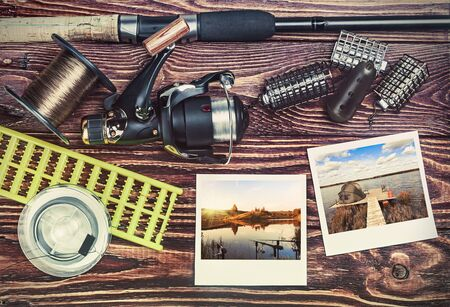 toned image: fishing tackle and photoframe on wooden table. toned image