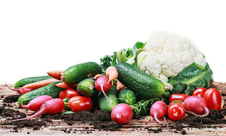 harvest vegetables on a wooden table isolated on white background photo