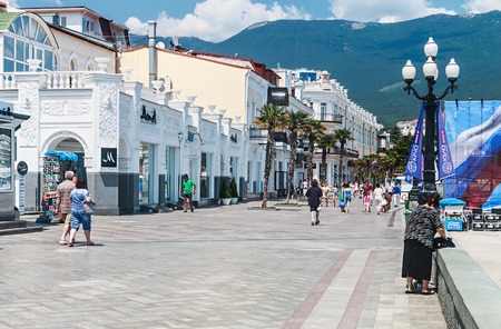 lenina: YALTA - June 10, 2014: People are walking along the Lenina Embankment. Lenin embankment central walking street of Yalta, one of the oldest streets in the city Editorial