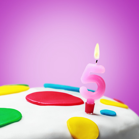 Burning candle with the number five on a birthday cake. birthday greetings photo