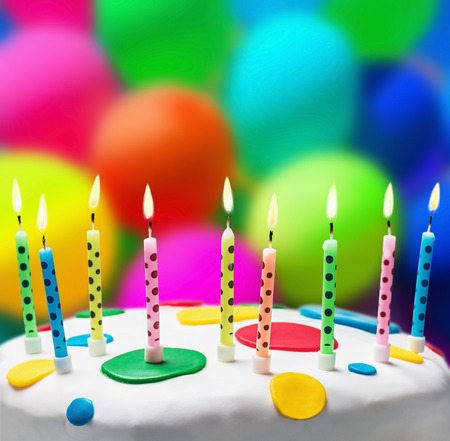 burning candles on a birthday cake on the background of balloons photo
