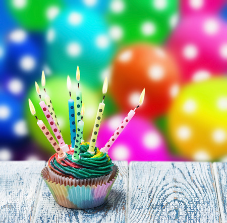 Birthday cupcake with burning candles on the background of balloons photo