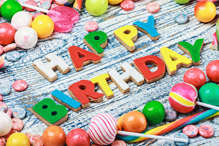 letters from happy birthday cookies and sweets and candies on the table photo