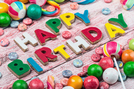 letters from happy birthday cookies and sweets and candies on the table. Focus on the first letter photo