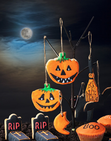 Halloween cookies hanging on a tree in the night sky photo