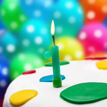 Burning candle with the number one on a birthday cake photo