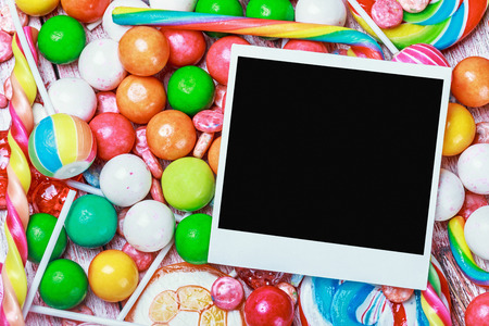 empty photo frame lies on sweets and candies photo