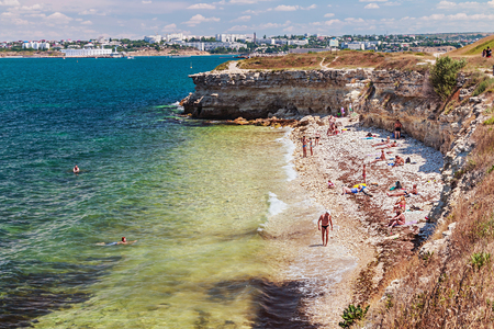 Sevastopol, Crimea - June 16, 2014:tourists basking on a wild beach of the ancient city of Chersonesos.Cherson esos based on the ancient Greeks Heracleian peninsula on the southwest coast of the Crimea