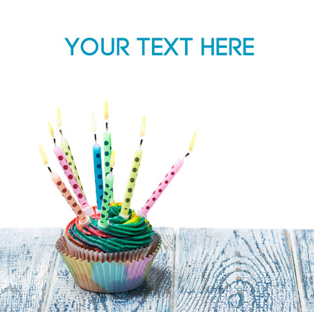 Birthday cupcake with burning candles on a white background. Empty white space above and below for sample background and text photo