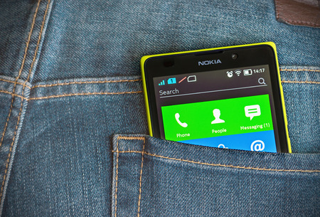 Moscow, Russia - August 26, 2014: Nokia XL smartphone in the pocket of jeans. Nokia XL new smartphone running on the Android platform with a 2-core processor Qualcomm.  報道画像