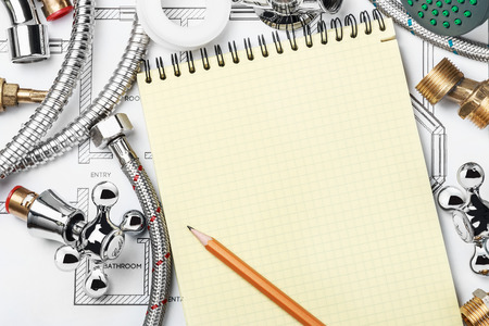 home maintenance: plumbing and tools with a notebook to write text