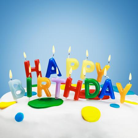 tortas cumpleaÑos: velas encendidas en una torta de cumpleaños Foto de archivo