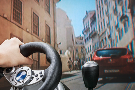 Teen playing in the race behind the wheel of a game console  Standard-Bild