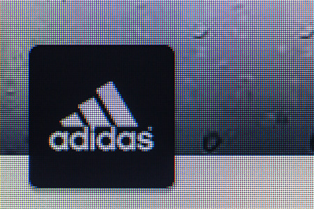adidas: Moscow, Russia - September 24, 2014: adidas logo on the screen of a computer monitor. Adidas German industrial group specializing in the production of athletic footwear, apparel and equipment.