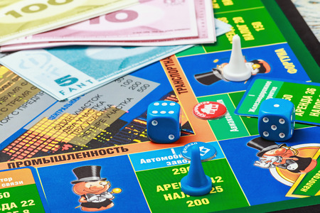 Moscow, Russia - September 11, 2014: Monopoly game on the table. Monopoly game in Russian, a board game in the genre of economic strategy for two or more people.