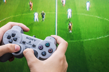 Moscow, Russia - September 11, 2014: Teenager playing football on the Playstation. Playstation game console of the fifth generation, developed by Sony Computer Entertainment Ken Kutaragi-led