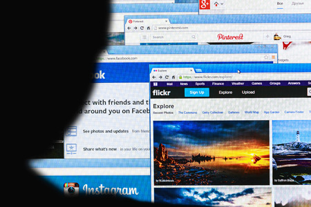 screenshot: Moscow, Russia - August 26, 2014: Moscow, Russia - September 24, 2014: Close-up open pages of social networking on a home computer screen with silhouette of a mans head out of focus in the foreground.  Editorial