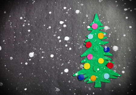 Christmas tree with toys made of felt and falling snowflakes photo