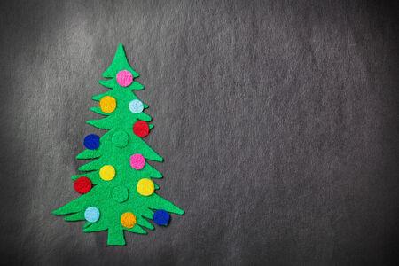 Christmas tree with toys made %u200B%u200Bof felt on a black  photo