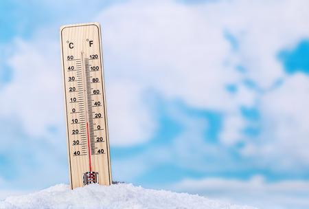 termómetro: Termómetro en la nieve contra el cielo con nubes