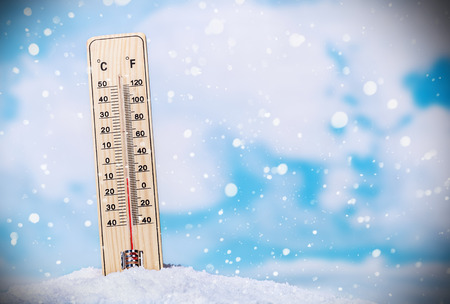 extreme weather: Thermometer on snow shows low temperatures on the sky with clouds Stock Photo