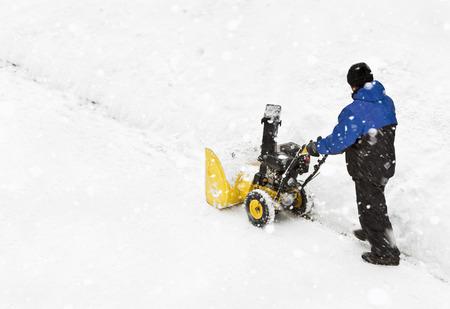 Hombre trabajando con una nieve soplando la máquina Foto de archivo - 34268441