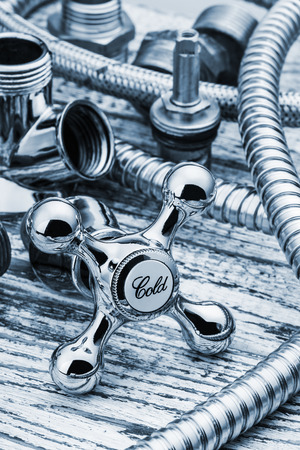 plumbing accessories: plumbing and accessories on wooden table. toned image