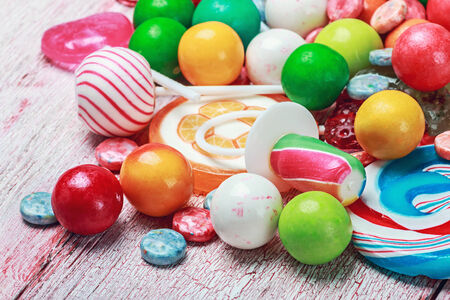 candy stripe: multicolored lollipops and candy on a wooden table