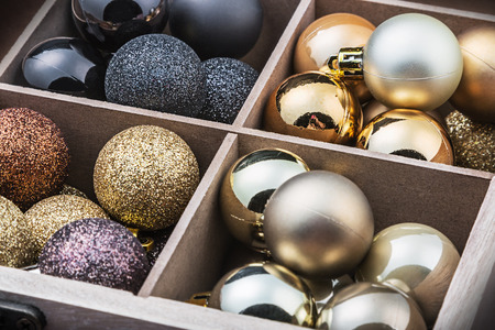 Wooden box filled with christmas balls. Focus on the yellow balls photo